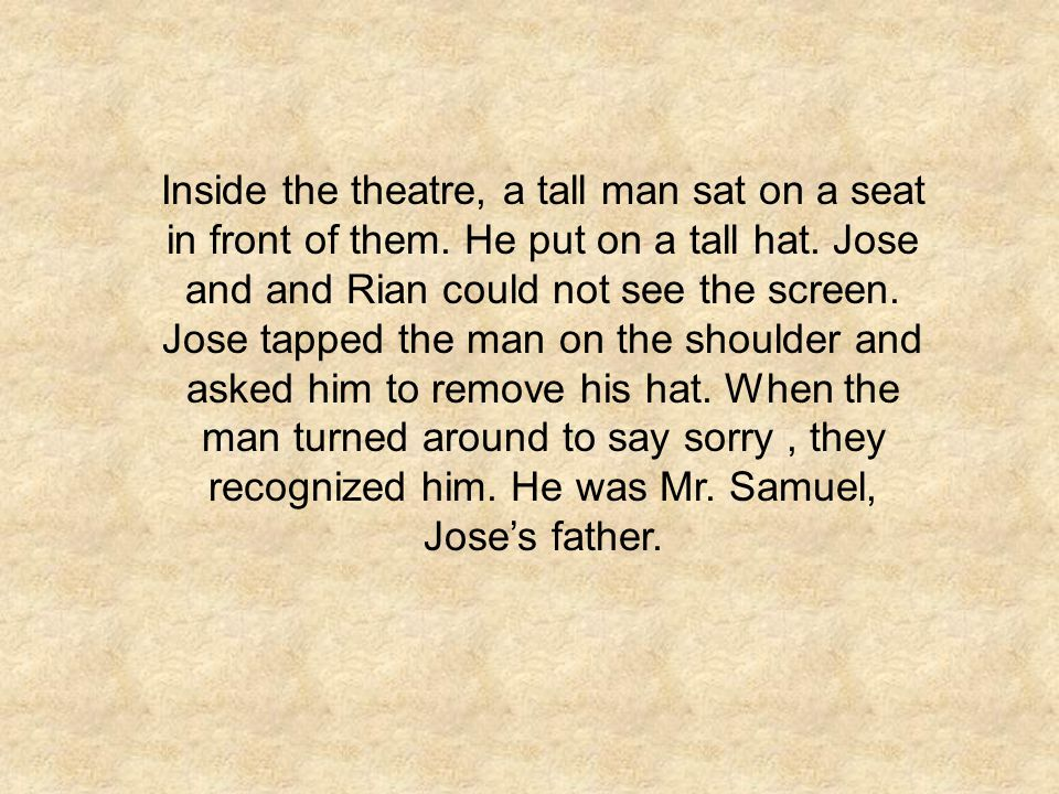 Inside the theatre, a tall man sat on a seat in front of them
