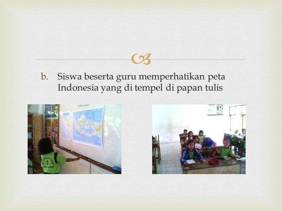 Siswa beserta guru memperhatikan peta Indonesia yang di tempel di papan tulis
